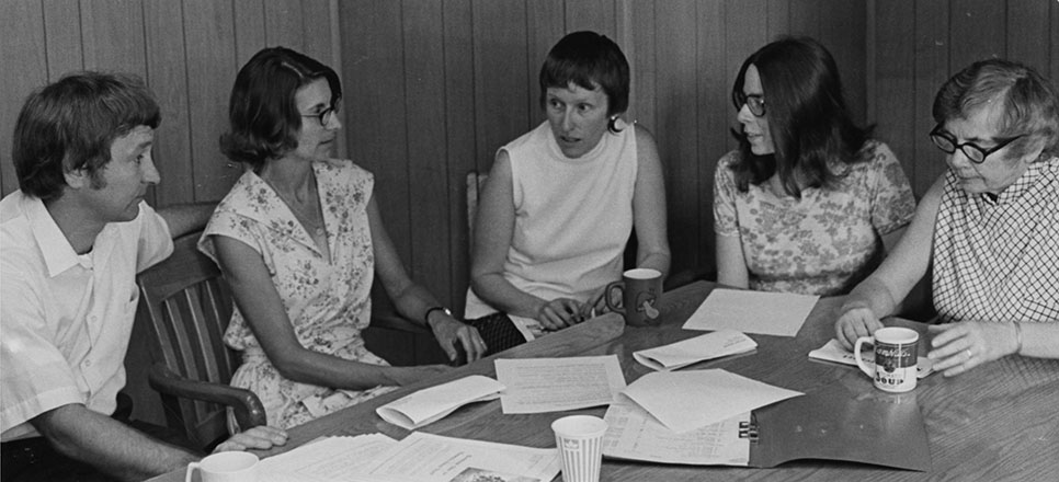 Founding Members of 8th Day holding a staff meeting, 1975