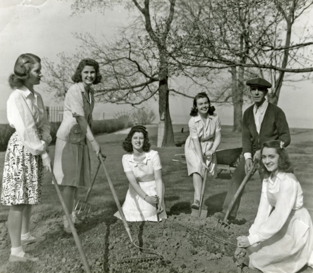 Mundelein College students help campus gardener, William McViffie plant a wartime garden in 1942.