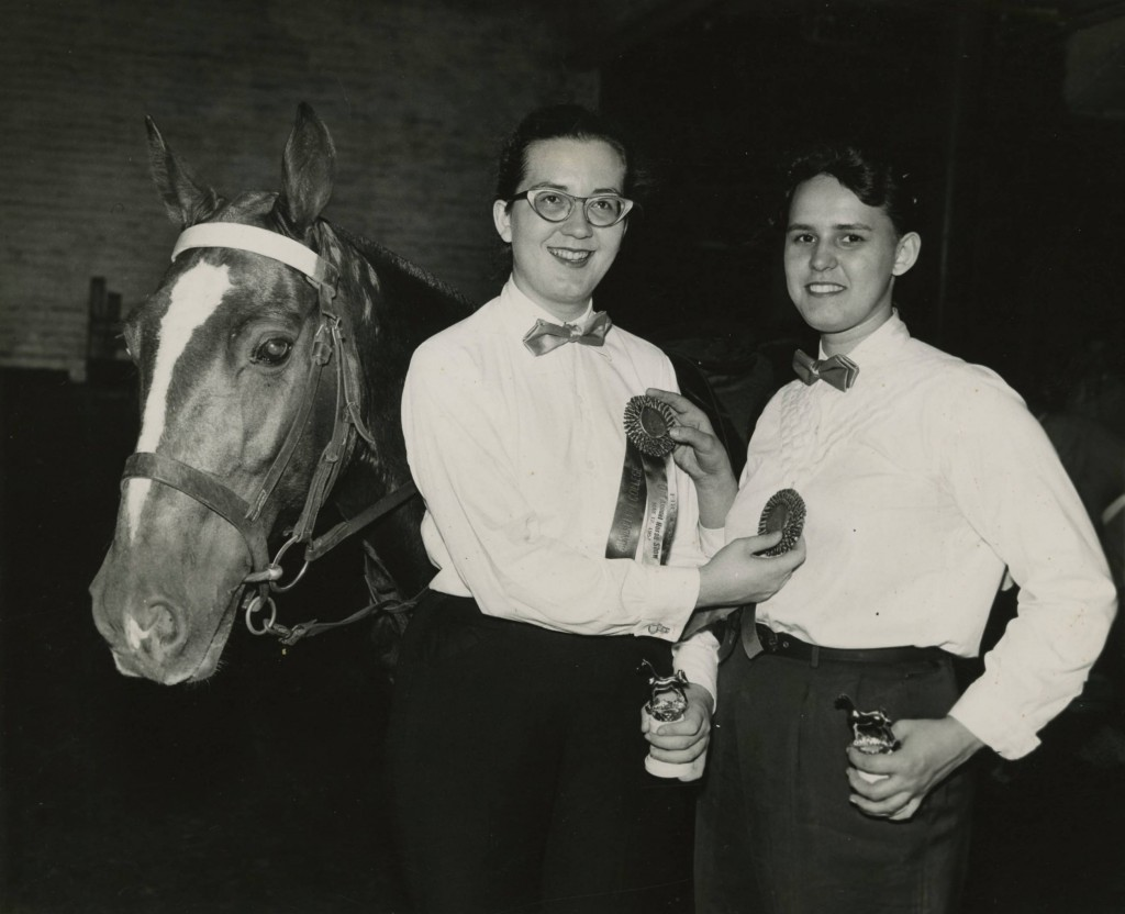 Horsemanship awards photo of 2 riders with horse posing with their trophies, undated. Mundelein Photograph Collection.