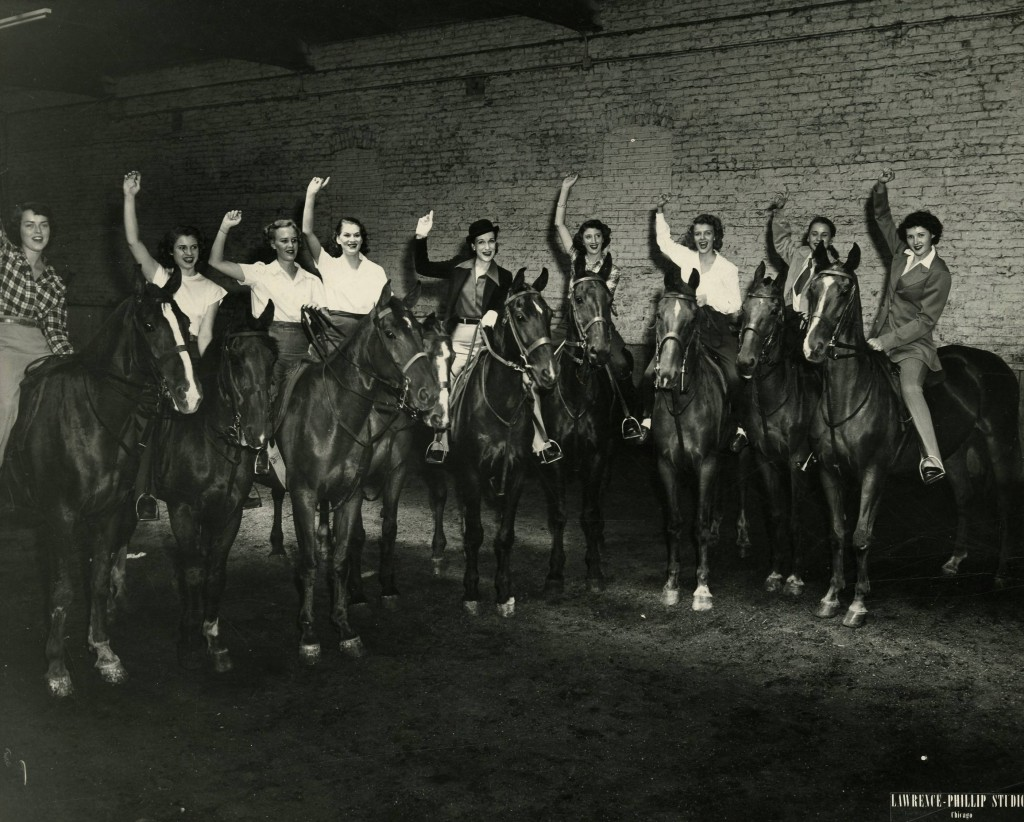 Group photo of Mundelein College Horseback Riding Club taken at Parkway Stables for the Annual Horse Show, 1940. Mundelein Photograph Collection.