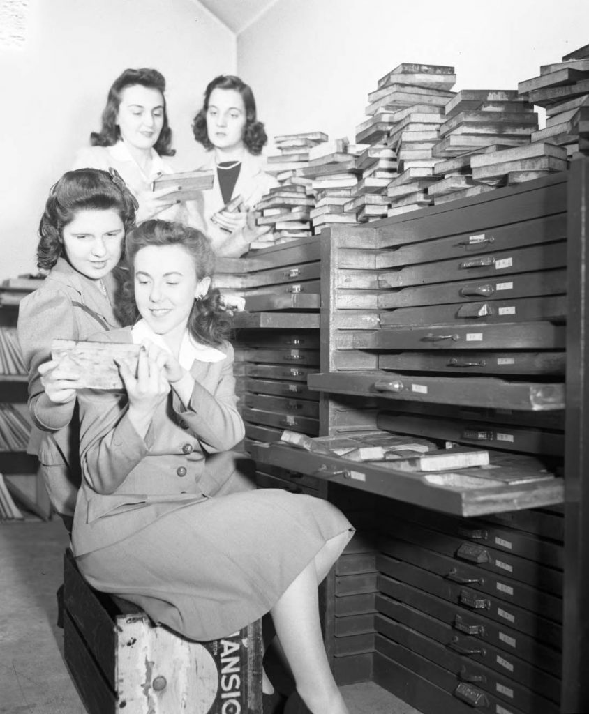 Student reporters review print blocks, 1942