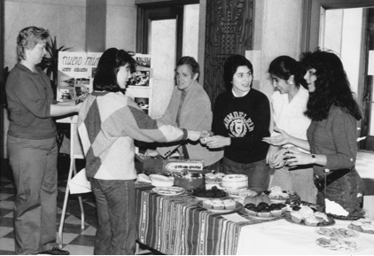 Figure 4. Kateri O'Shea, BVM (behind the counter, first from left) and three unidentified students conduct a bake sale, 1985 (WLA, Mundelein College Photograph Collection).