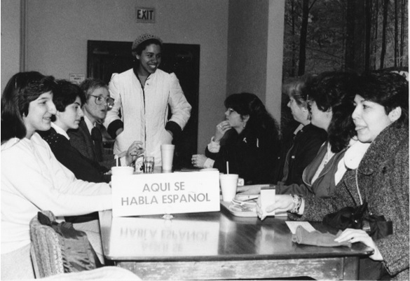 Figure 5. Kateri O'Shea, BVM, speaks Spanish with Maria Castano and Michelle Mulcahy at a Spanish table with five other unidentified students in the Tea Room at Mundelein College, 1985 (WLA, Mundelein College Photograph Collection).