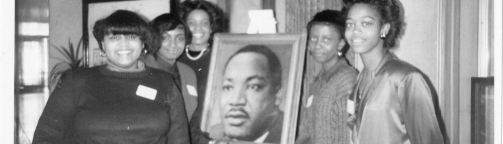Five individuals posing with a portrait of Martin Luther King, Jr.