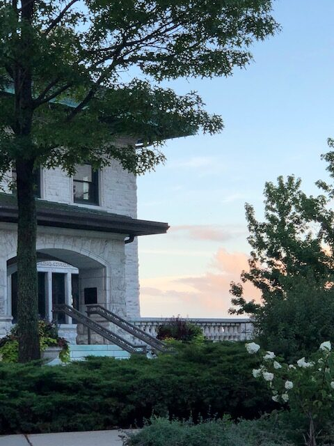 Pink clouds and a blue sky glow in the distance beyond Piper Hall's main stairs, with green foliage in bloom in the foreground.
