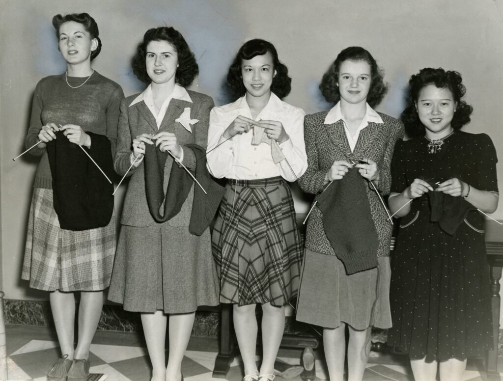 Five Mundelein College students dressed in 1940s fashions stand in a line and hold their knitting projects.